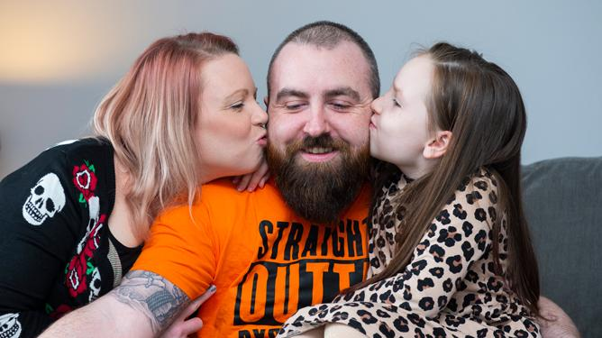 A man with a bead and bright orange t-shirt poses with his wife and daughter either side of him planting a kiss on his cheeks.