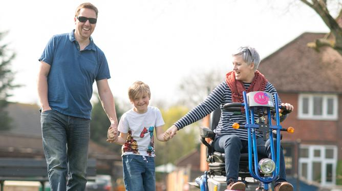 A woman living with LGMD and who uses a mobility scooter holds hands with her son while her husband holds his other hand