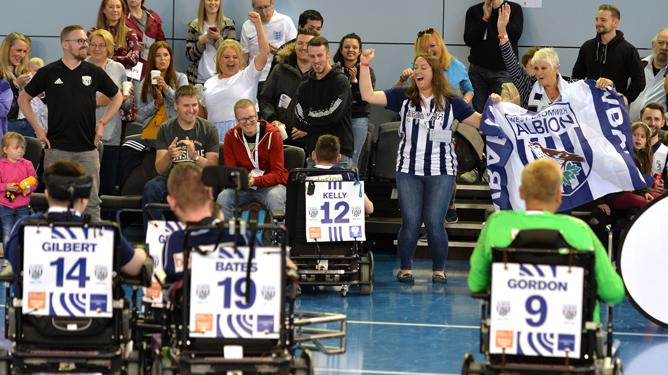 Five people in powerchairs taking part in a powerchair football match in a sports hall while spectors cheer animatedly in the background