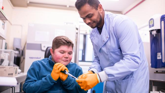 A teenage boy assists a researcher wearing a lab coat and gloves with some testing in a laboratory.