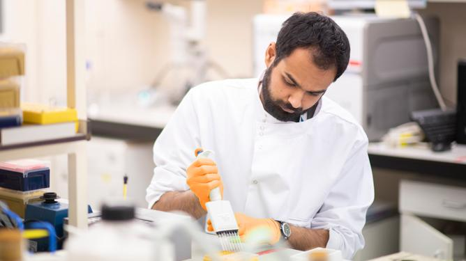 A researcher wearing safety goggles and a lab coat conducts tests in a laboratory.