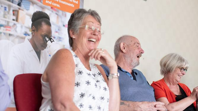 Two women and a man laughing while seated together at an MDUK Muscle Group.