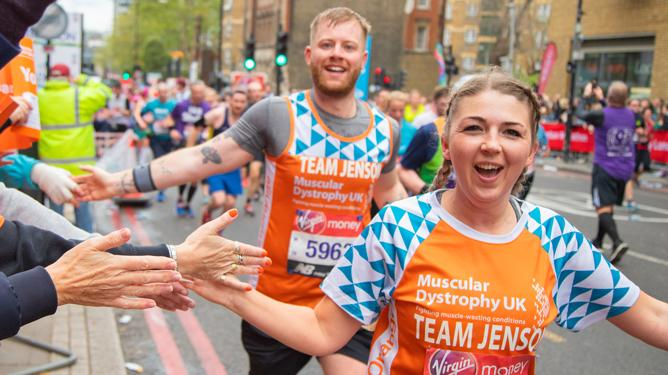 A young female runner accompanied by a young male runner, high five spectators while running the Virgin London Marathon in their MDUK t-shirts.