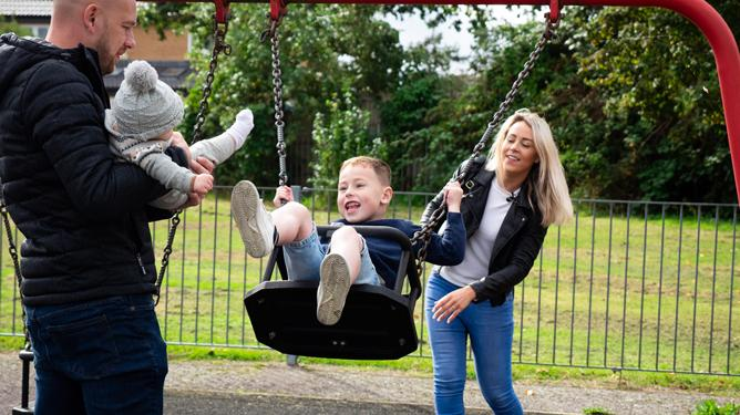 A father holds a young baby while a mother pushes her young son, who has Duchenne muscular dystrophy, on a swing.