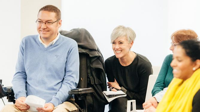 A man in powerchair sits next to four other female participants while taking part in a workshop.