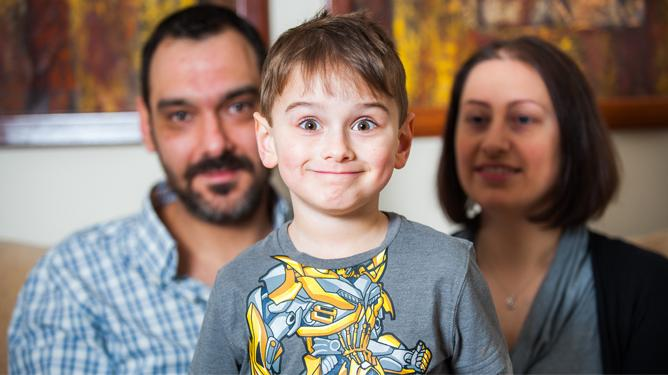 Young boy who has Duchenne muscular dystrophy smiles with his parents