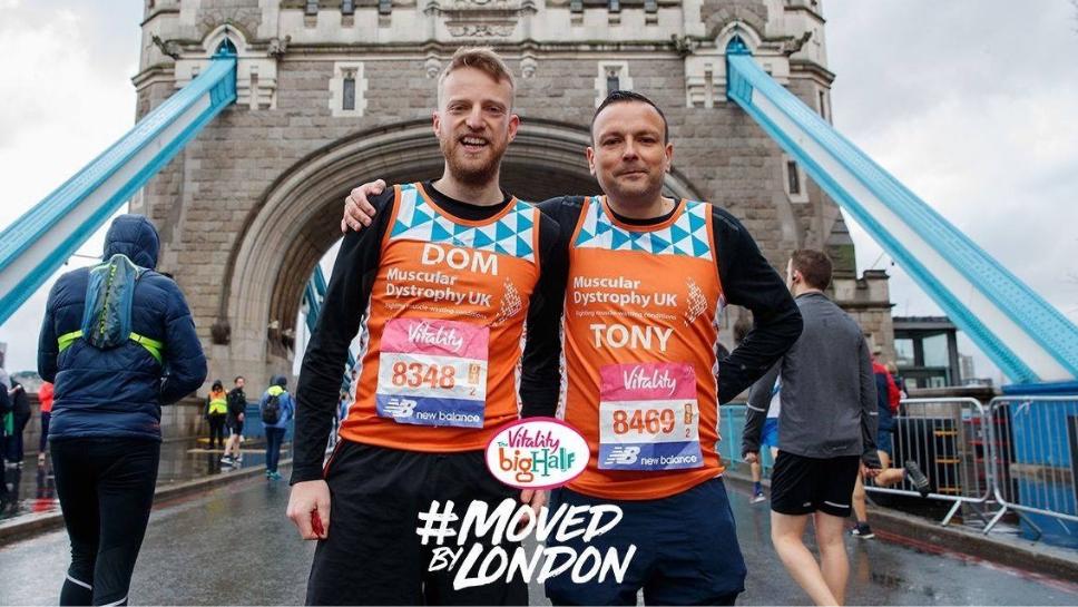 Two #TeamOrange runners standing on Tower Bridge at the Big Half in 2019