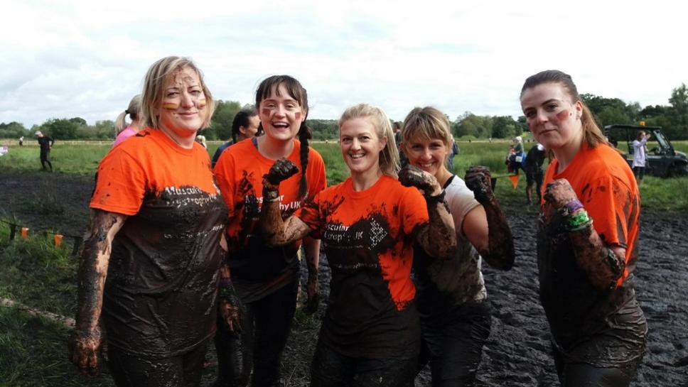 Group of women covered in mud