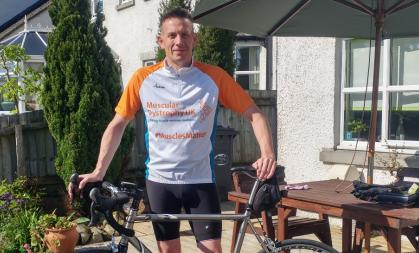 Man dressed in cycling gear standing with bicycle