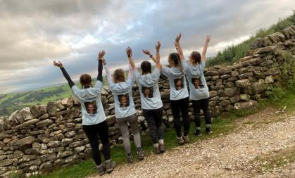 Five women throwing there hands into the air in the countryside